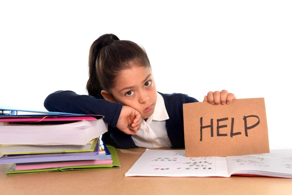 sweet little female latin child studying on desk asking for help in stress with a tired face expression in children education and back to school concept isolated on white background